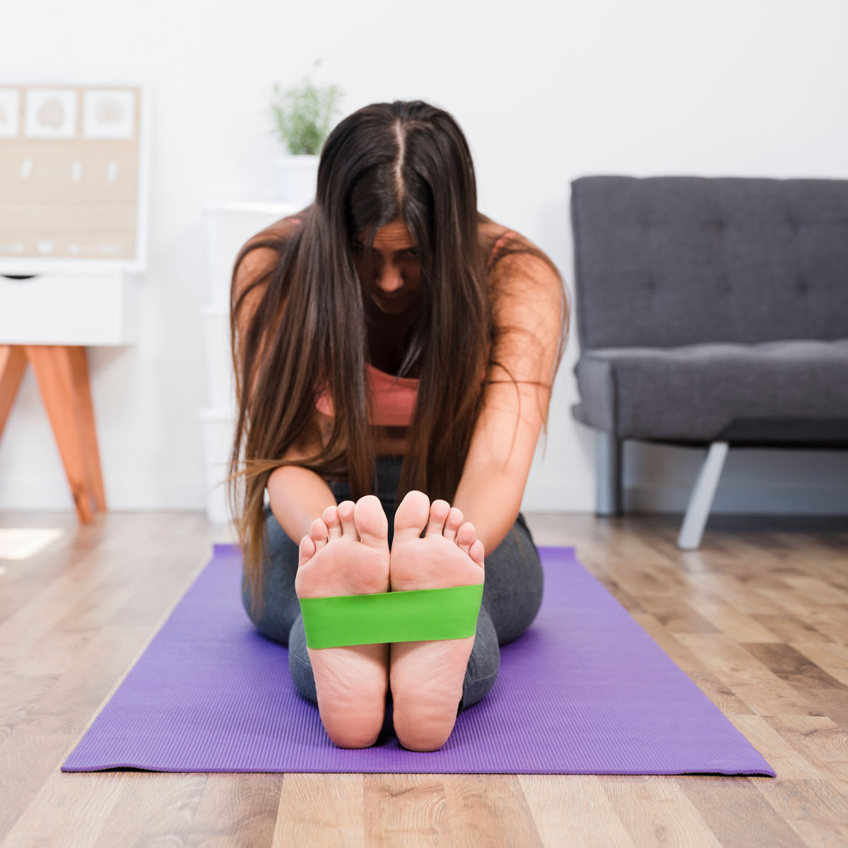 Photo of woman sitting using a Yoga prop to stretch